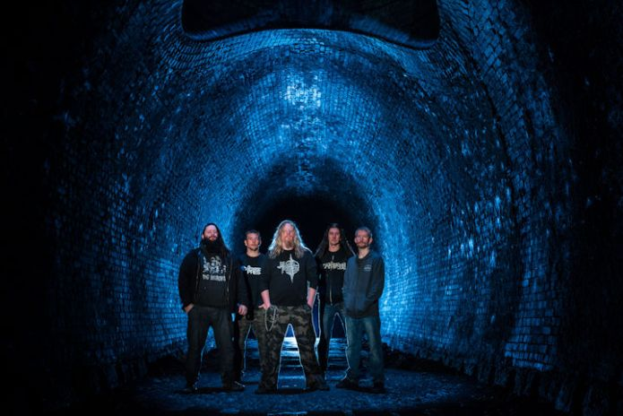 Krysthla band promo photo standing in a tunnel that has been lit blue